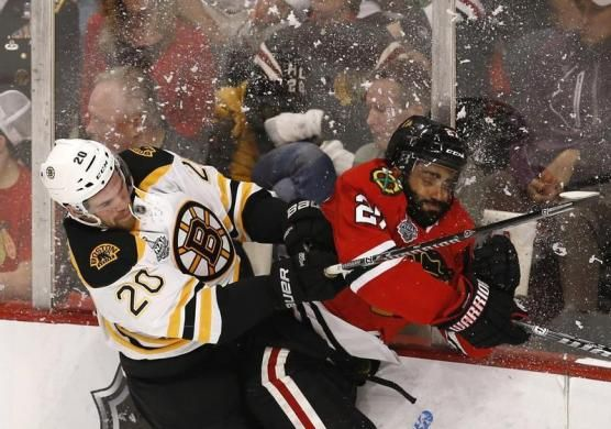Boston Bruins' Daniel Paille (L) checks Chicago Blackhawks' Johnny Oduya during the first period in Game 1 of their NHL Stanley Cup Finals hockey game in Chicago, Illinois, June 12, 2013. REUTERS-Jim Young (UNITED STATES  - Tags: SPORT ICE HOCKEY TPX IMAGES OF THE DAY)