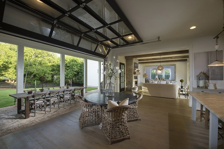 A Stunning Glass Roll Up Door Connects This Kitchen To The Outdoor Dining Area Beyond Modern Home Interior Ideas Midcentury Glass House Design Glass
