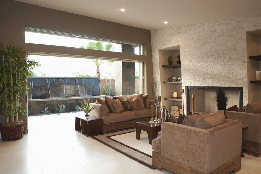 Modern Look Living Room Features Expansive Gl Wall To Outside Fountain Along With Unique Wood And Cloth Brown Chairs Over White Tile Flooring