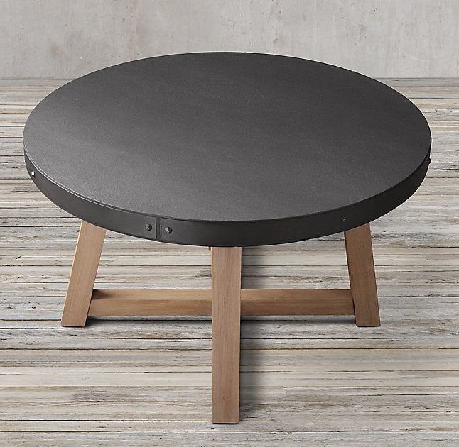 "RH's Salvaged Wood & Concrete Beam Round Dining Table:Our table pairs a 3""-thick slate grey concrete top with the natural beauty of solid salvaged pine timbers from 100-year old buildings in Great Britain."