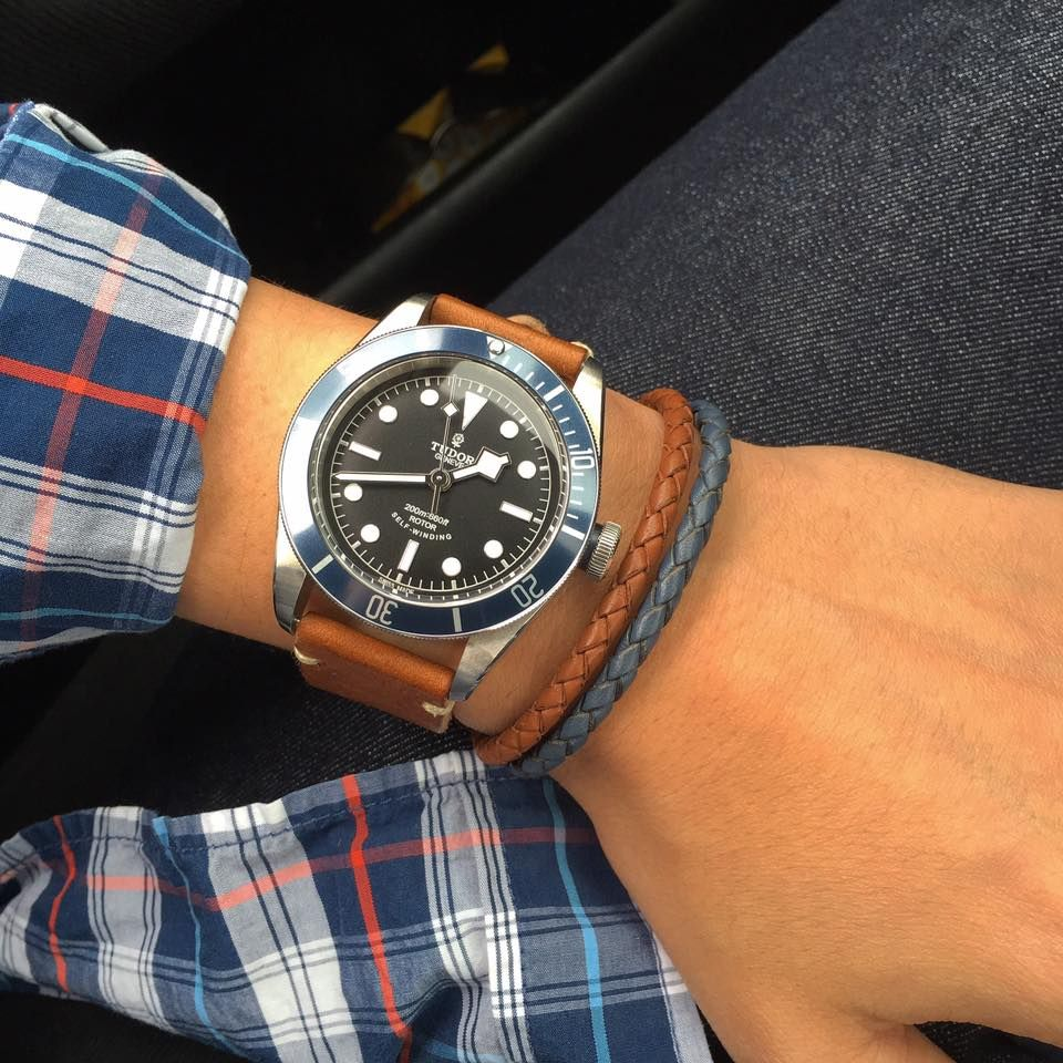 Tudor Heritage Black Bay Blue with a tan leather strap and matching leather bracelets.