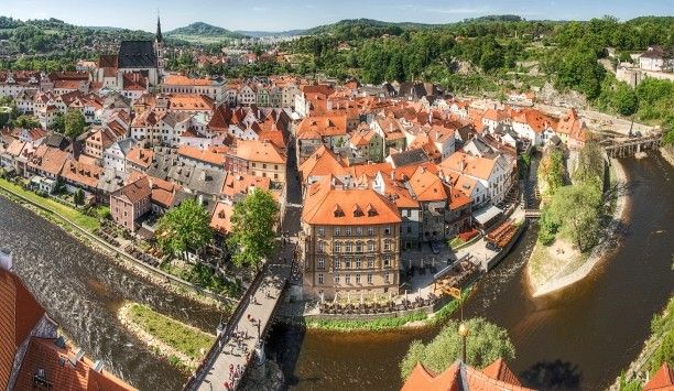 Prague to Budapest Tour: Sip Moravian white wine on a riverside terrace in the scenic Czech city of Cesky Krumlov.