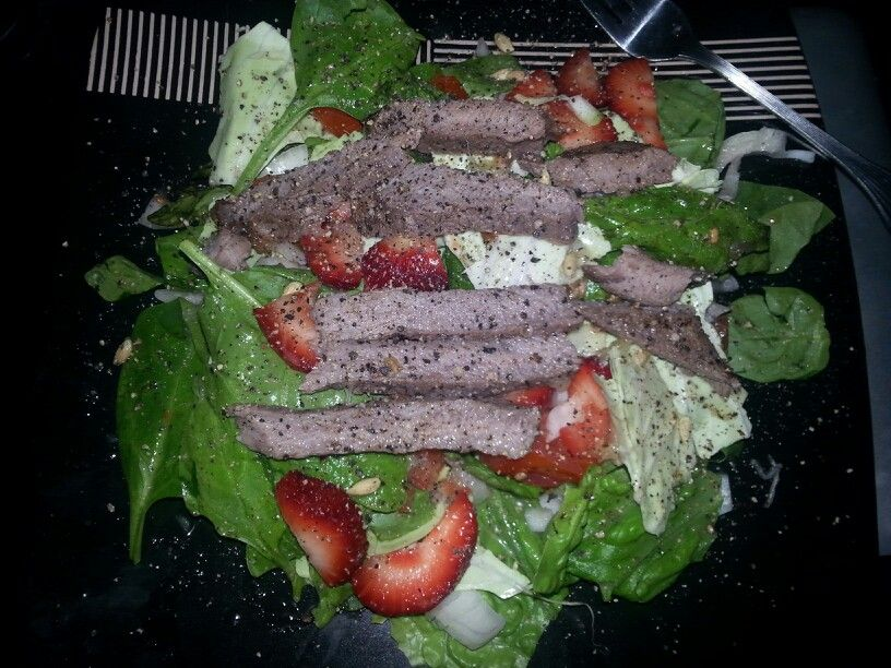 Strawberry Montreal steak salad - spinach, romaine lettuce, cabbage, tomatoes, onion, strawberries,  cooked in olive oil and Montreal seasoning sirloin steak, lemon juice and pepper dressing. Yum!