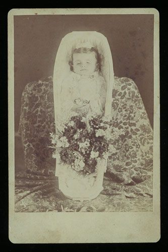 A cabinet card photograph of a young girl in her casket, taken about 1870.