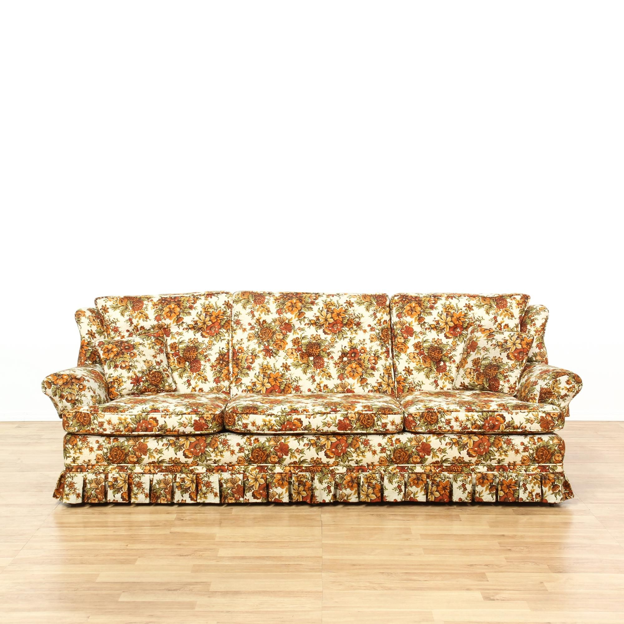 This Sofa Is Upholstered In An Orange Floral Pattern. This Traditional  Style Couch Has Matching Throw Pillows, A Skirted Base, And Plush Cushions.