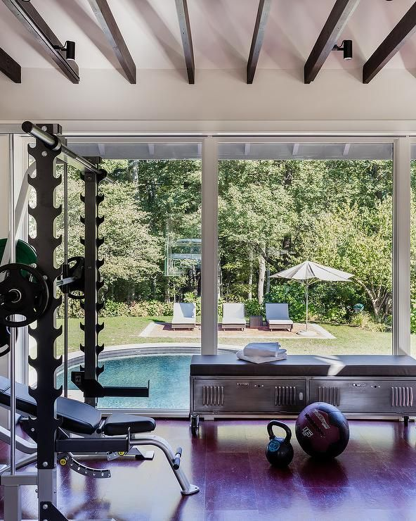 Overlooking A Backyard With An In Ground Pool This Stunning Home Gym Is Equipped With A Stainless Steel Bench Pla Gym Room At Home Home Gym Design Pool Houses