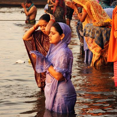 7e855cd41ac Varanasi, India. Women praying to their gods to wash their sin away in the Ganges  River.