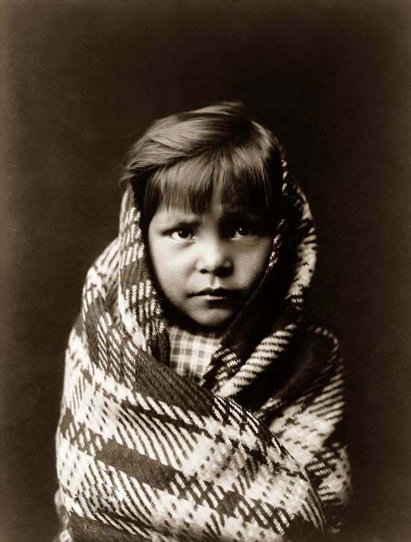 You are looking at an educational picture of a Navajo Child. It was taken in 1905 by Edward S. Curtis.    The picture presents Ia touching portayal of a Native American wrapped in a blanket.