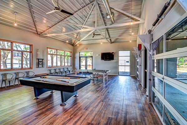 High Ceiling Game Room With Industrial Seating And Garage Doors