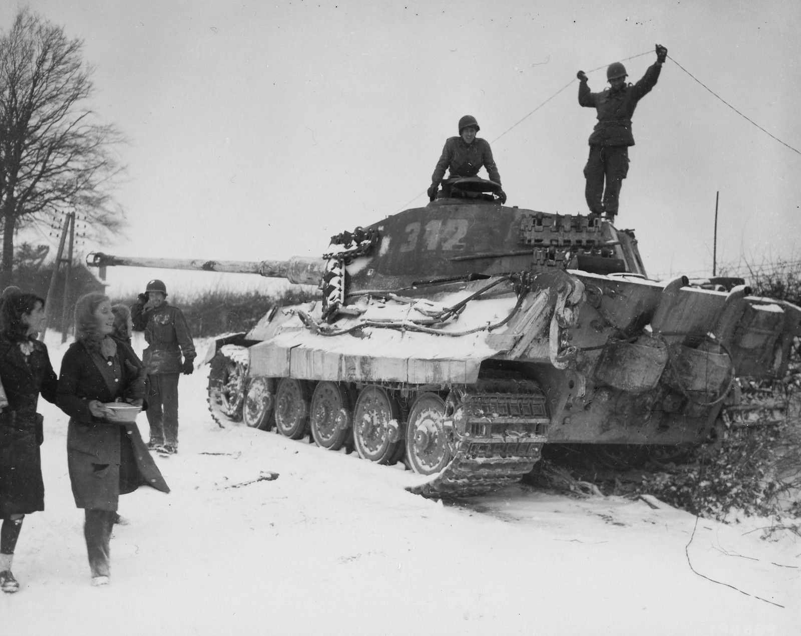 American soldiers of the 82nd Airborne Division inspect a disabled German Tiger II tank and admire two passing girls near the village of Corenne, Belgium (February 1945). The soldier at the top right is stringing wire for field phones.