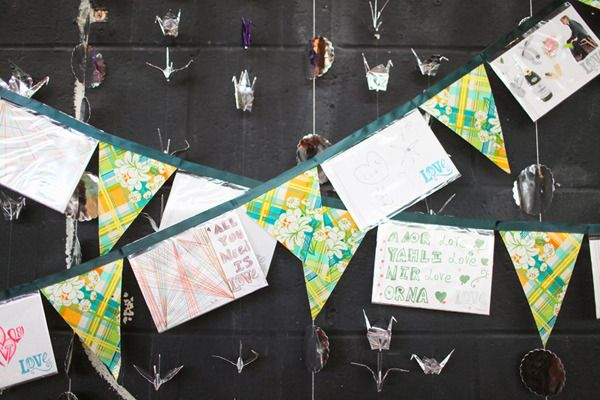"This is cute! From the bride, ""Our guests also contributed to the wedding decorations! We left a blank space in the design on the front of our postcard RSVP's & asked our guests to share their creativity with us. It was so much fun receiving the postcards & seeing all the designs & messages! Our bridesmaid took the RSVP cards & made them into bunting, which were hung on a focal wall in the reception area, along with some of the 1,001 cranes we folded!"" Photography by adriennegunde.com"