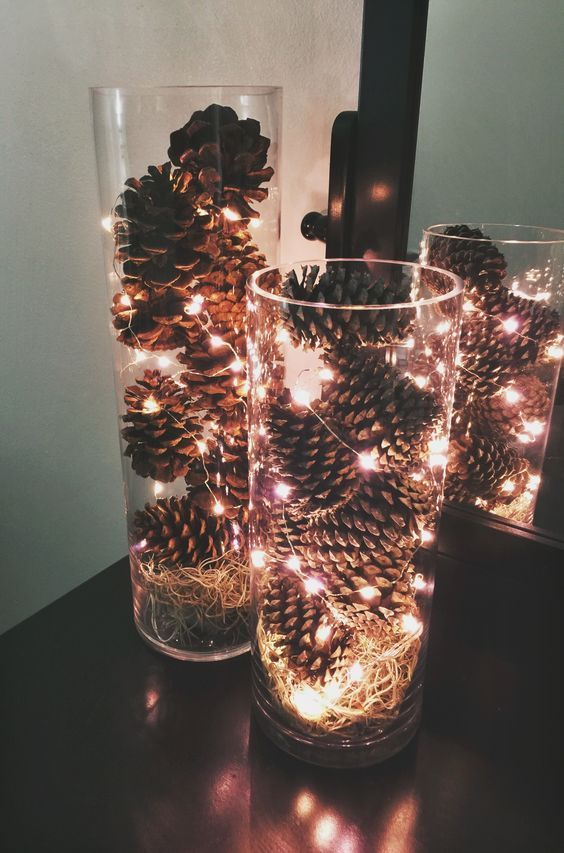 Une jolie déco de Noël avec un vase, des pommes de pin et des guirlandes  lumineuses.