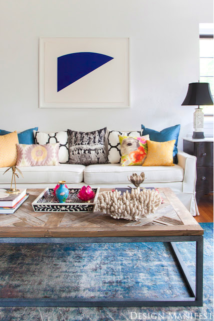 White walls, colorful accessories! Over-dyed vintage bright blue rug, blue, apricot, yellow, orange, pink, black, white grey and driftwood. Graphic contemporary art over the sofa.
