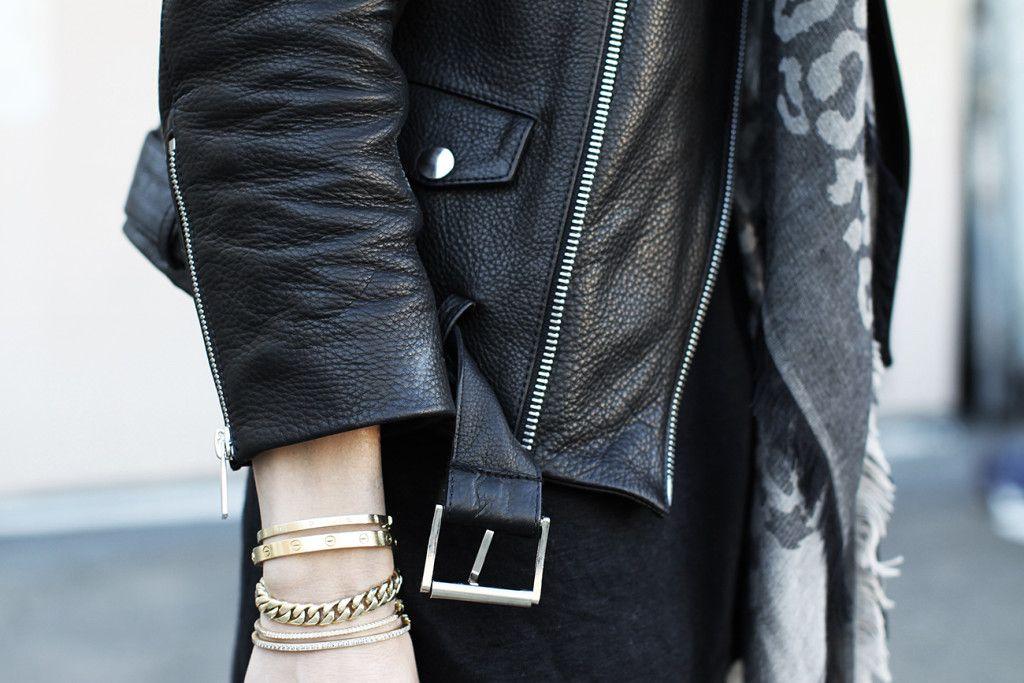 pulseiras douradas em look com jaqueta de couro preta
