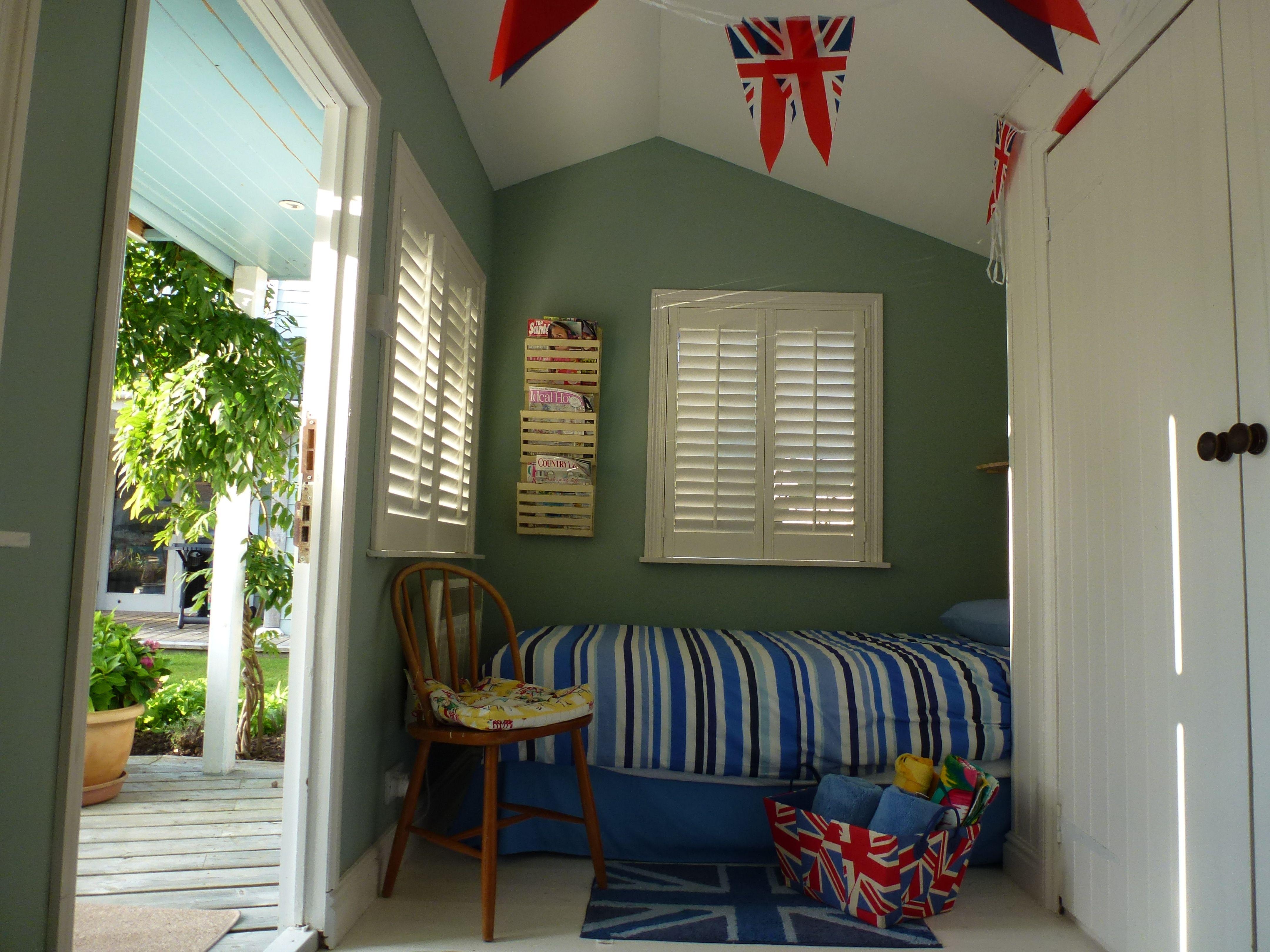 poolside cabin with Tesco bunting, Matalan bedlinen. TK Maxx magazine rack, Dunelm Mills rug & Union Jack storage box, charity shop chair with 50's retro cushion