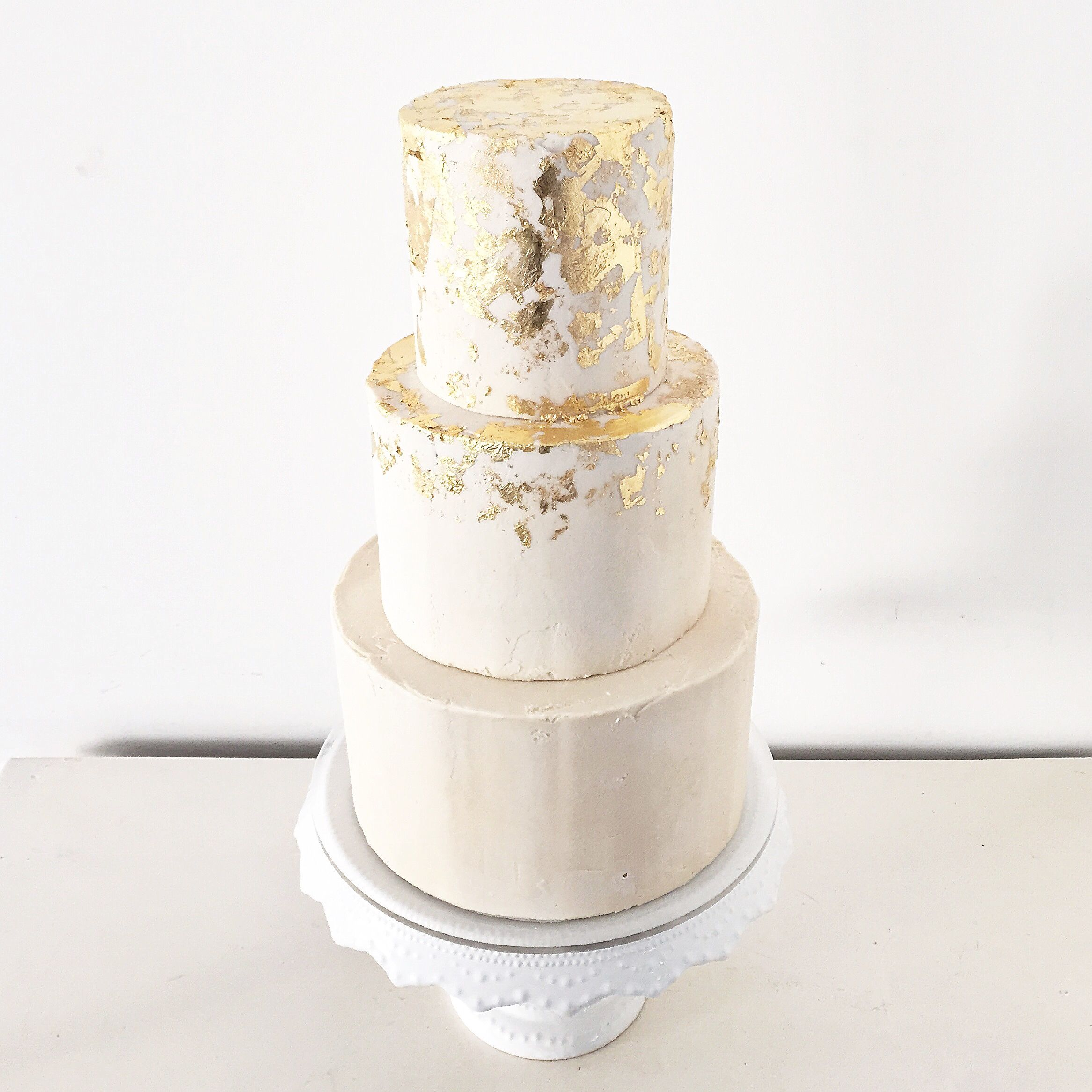 Three tier buttercream wedding cake with distressed gold