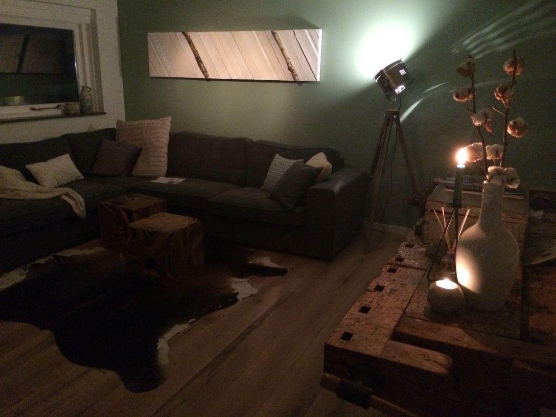 Werkbank als Side table. Koeienvacht kleed en kleine houten salontafeltjes.