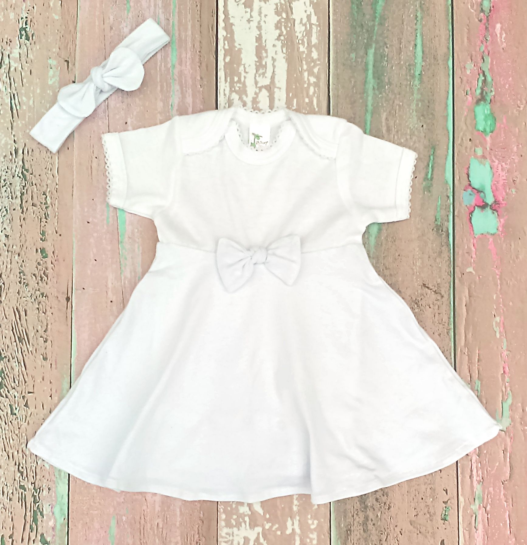 This white infant dress makes a minimalist and modern baby girl