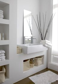 All white bathroom with open storage space