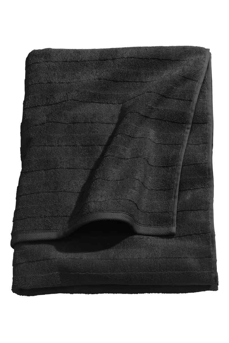 Bath towel: Bath towel in thick cotton terry with a woven textured stripe. Hanger on the short sides.