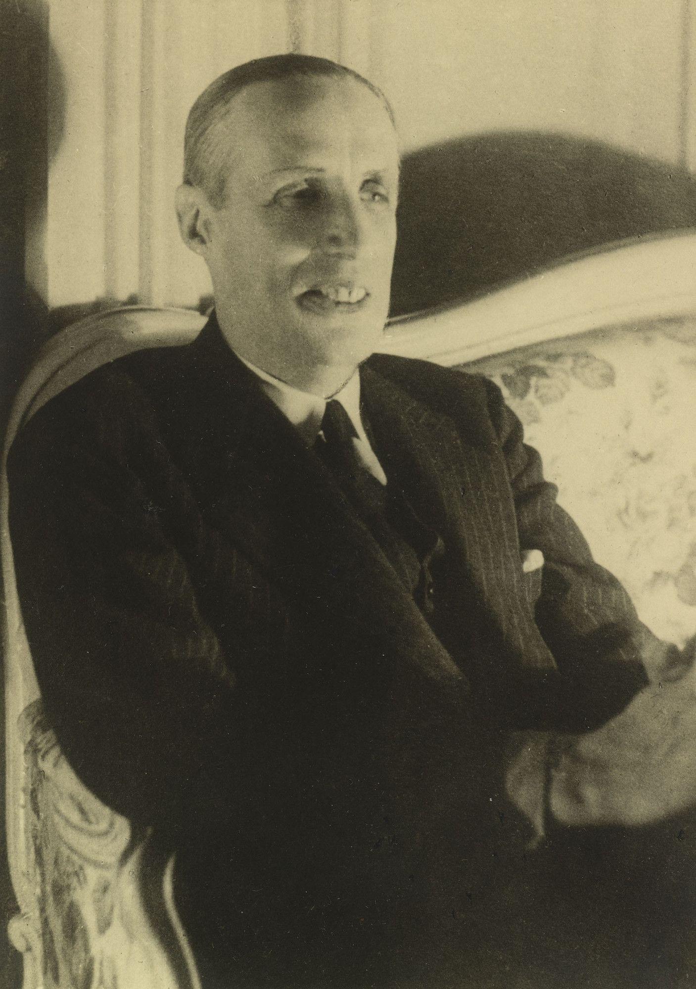 Reprodução de uma fotografia original do Príncipe Gabriel Constantinovich em cerca de 1950. Ele está sentado em um sofá, voltado ligeiramente para a direita. Ele está vestindo um terno escuro e gravata.
