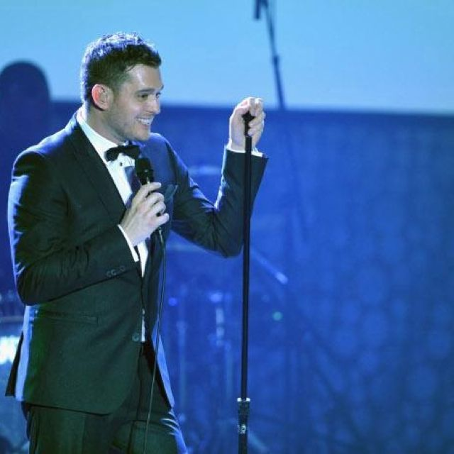 To sing like Michael Buble  in a crowd wearing same suit, sitting on a high chair with spotlight.
