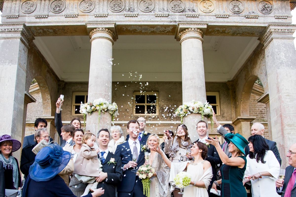 Celebrating guests throw confetti as the happy couple leave the Temple after the wedding ceremony. The Temple is licensed for civil ceremonies and provides a romantic location with the inspiring backdrop of Holkham park, making your day even more special. Photo courtesy of Katherine Ashdown. www.holkham.co.uk