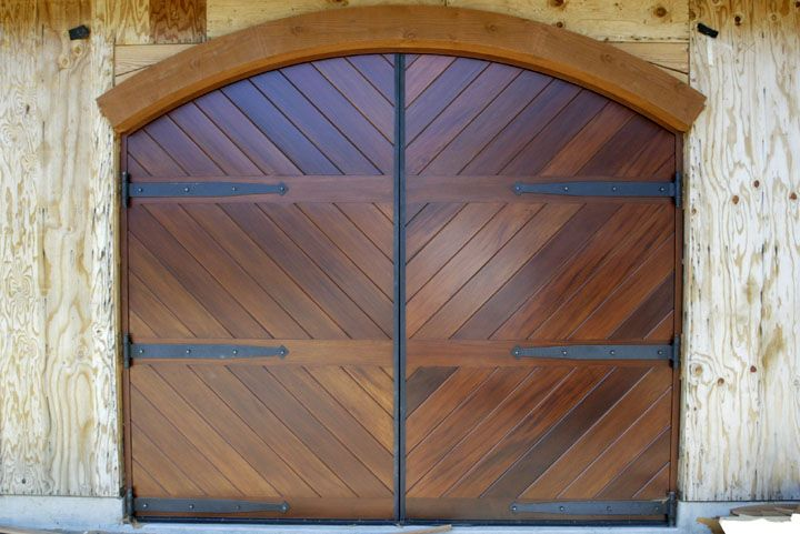 Curved wooden lintel strap hinges and gorgeous wood make for Wood garage door manufacturers