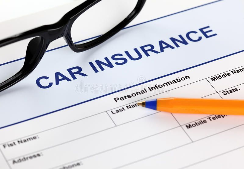 Car insurance application form with glasses and ballpoint