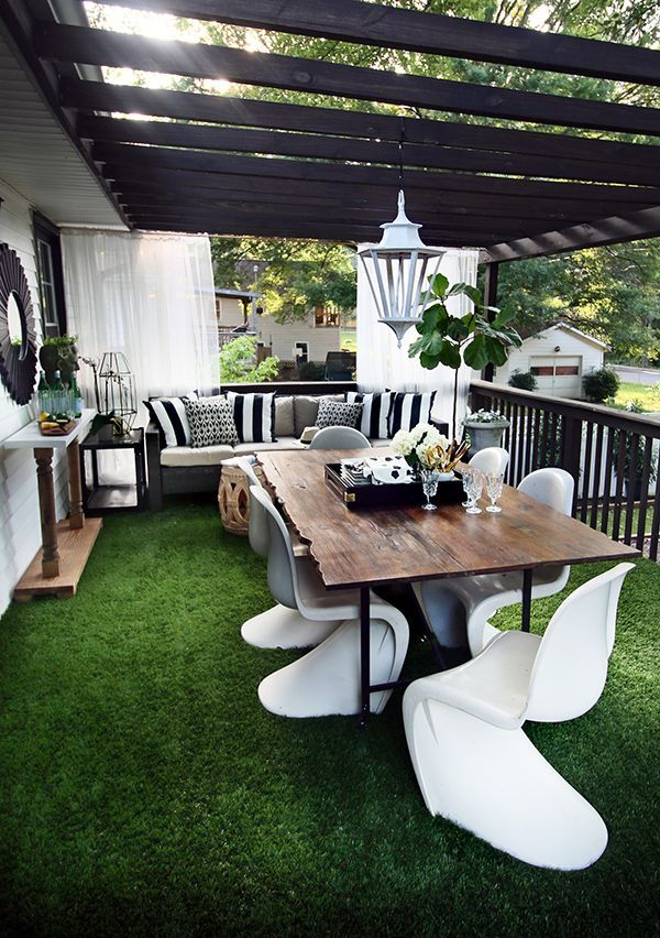 Terrace with artificial grass White chairs with wooden top table