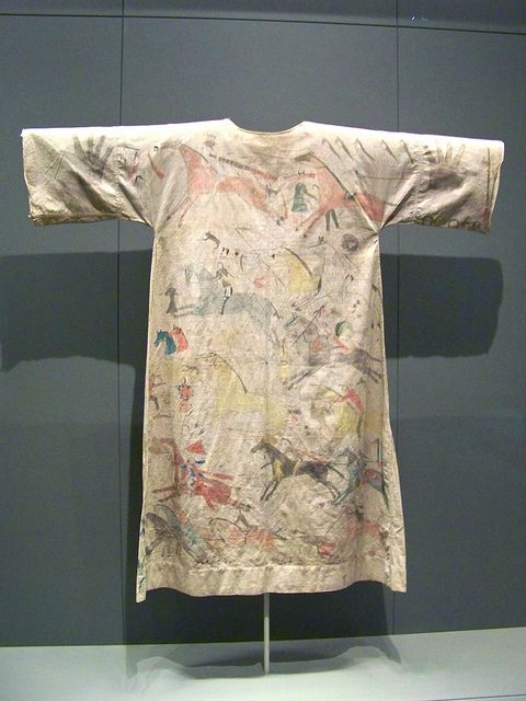 Pictographic dress. Graphite & pigment on muslin, circa 1885. Lakota (Teton Sioux). Among the Lakota, dresses with battle scenes could be worn only by women who had lost relatives in war. This dress belonged to Silent Woman (Ini'laon'win), sister of Bobtail Bear, who was killed in battle with the Crow.