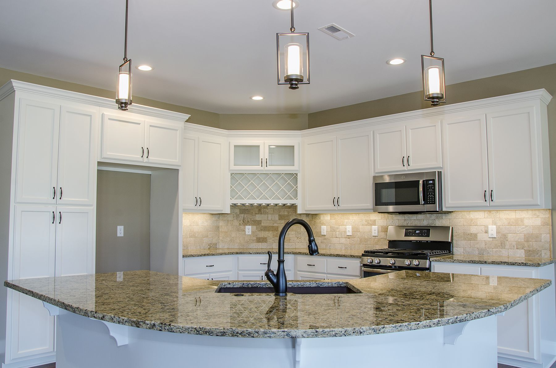 Beautiful L Shaped Kitchen With White Cabinets Granite Countertops And A Curved Island With Sink Gr L Shaped Kitchen Designs L Shaped Kitchen Kitchen Design