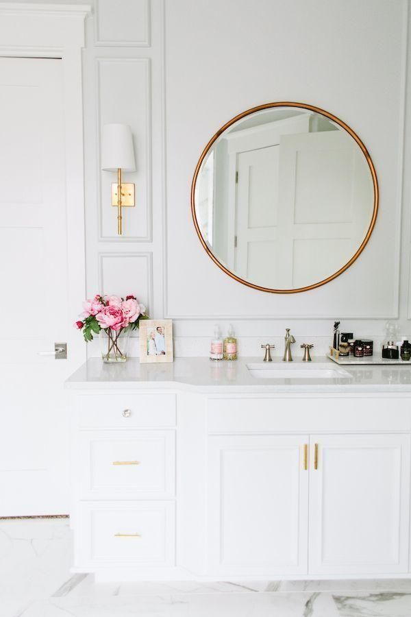Gorgeous feminine all-white bathroom with brass fixtures and pretty pink roses. Perfection!