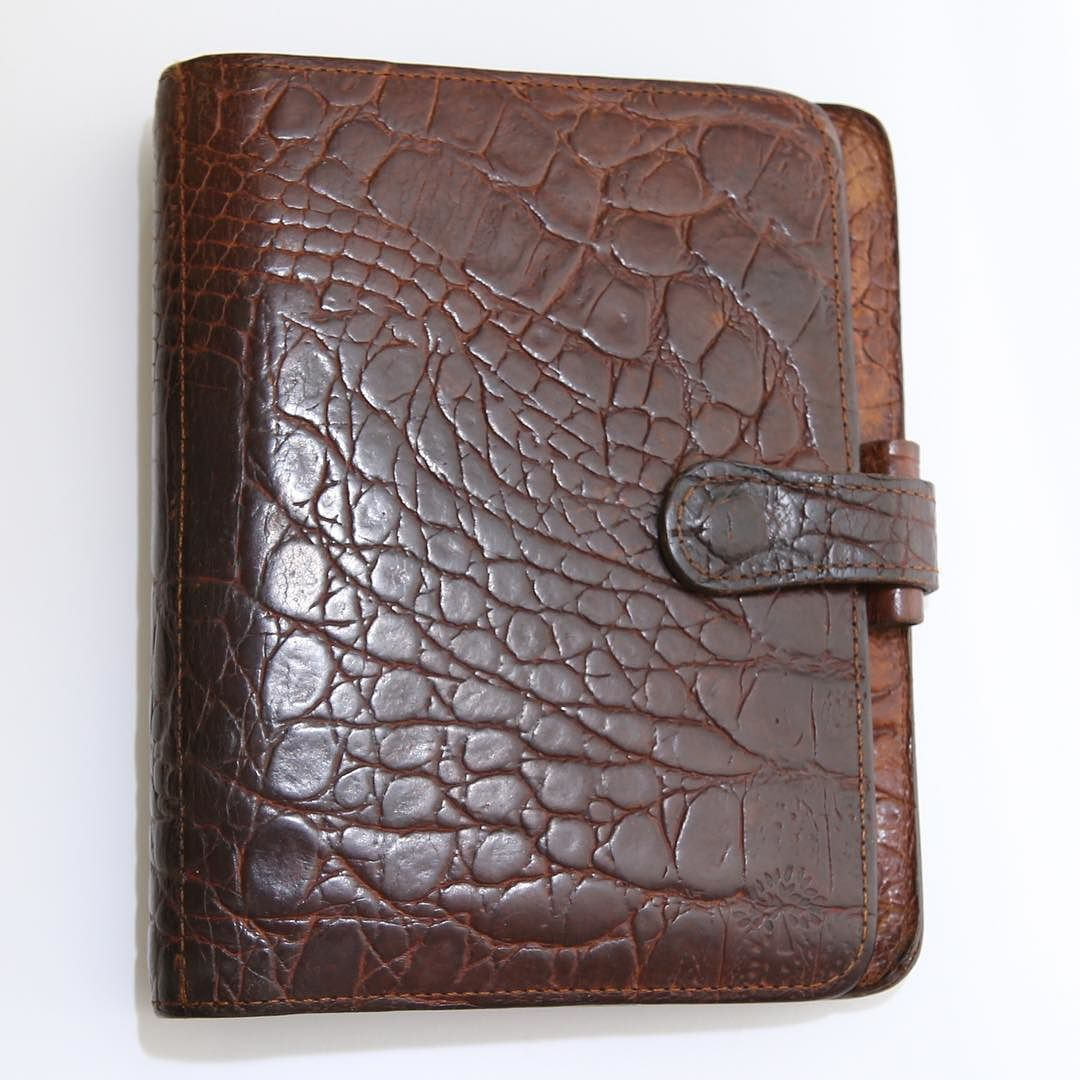 AVAILABLE Mulberry Croco Agenda Leather Crocodile Print Brown A6 Filofax Krause VINTAGE  Material: Calf leather with crocodile print Color: Brown Size: A6 Features:  On the left: 3 credit card pockets secretarial pocket full-height pocket On the right: zipped full-height pocket  With a leather pen loop and leather strap popper not visible double snap closer in front Dimensions:14cm x 3cm x 18cm Ring Size: 23mm (KRAUSE rings)  In preloved and used condition. With various marks on the leather…