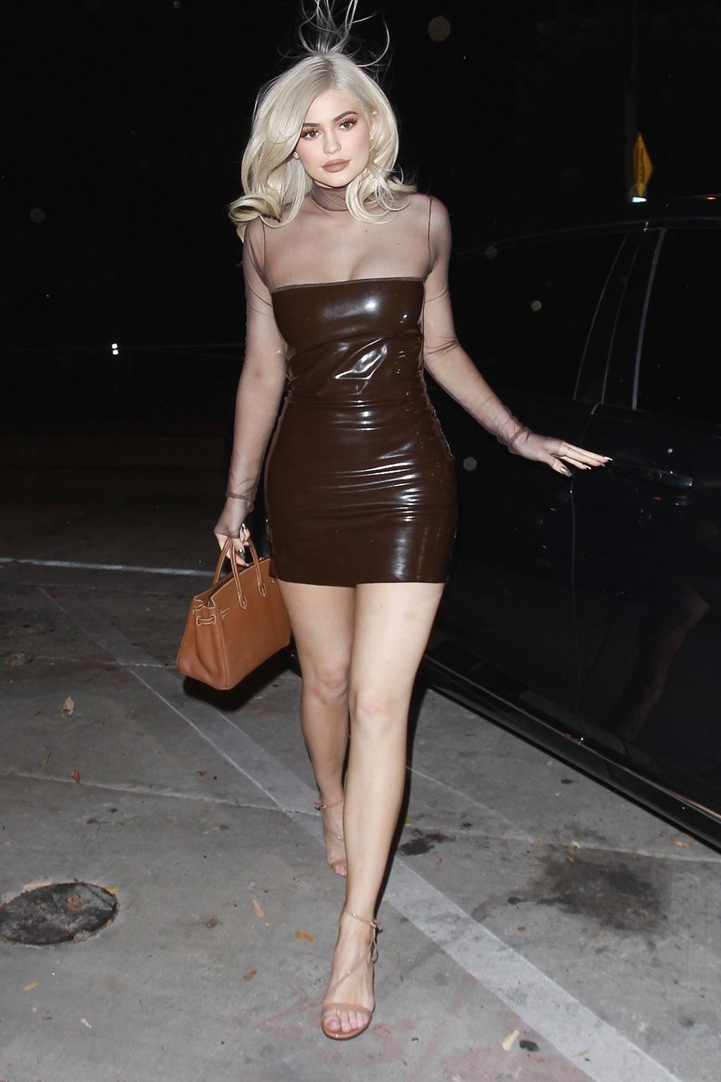 16a2efc80ff Kylie Jenner s date night outfit included a brown latex mini dress with a  sheer top.