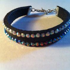~~Bracelet en simili cuir noir avec demies perles incrustées; Il se décline en deux couleurs:: une bleue et une blanche les deux avec reflets brillants une chaîne de finition permet un réglable a toutes les tailles de poignet avec une breloque en forme...