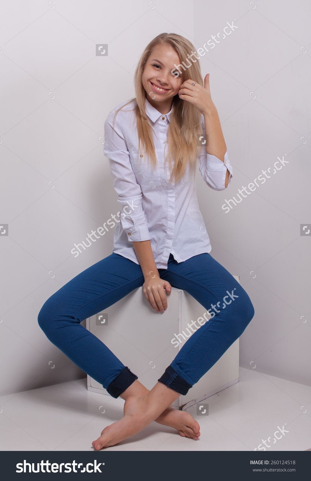 Blonde Young Woman In Ragged Jeans And Vest Sitting