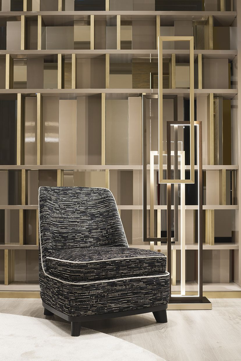 Eveline armchair and Edge floor lamp. Aback Magrit bookcase, whose distinguishing feature is the irregular pattern with which the spaces are arranged