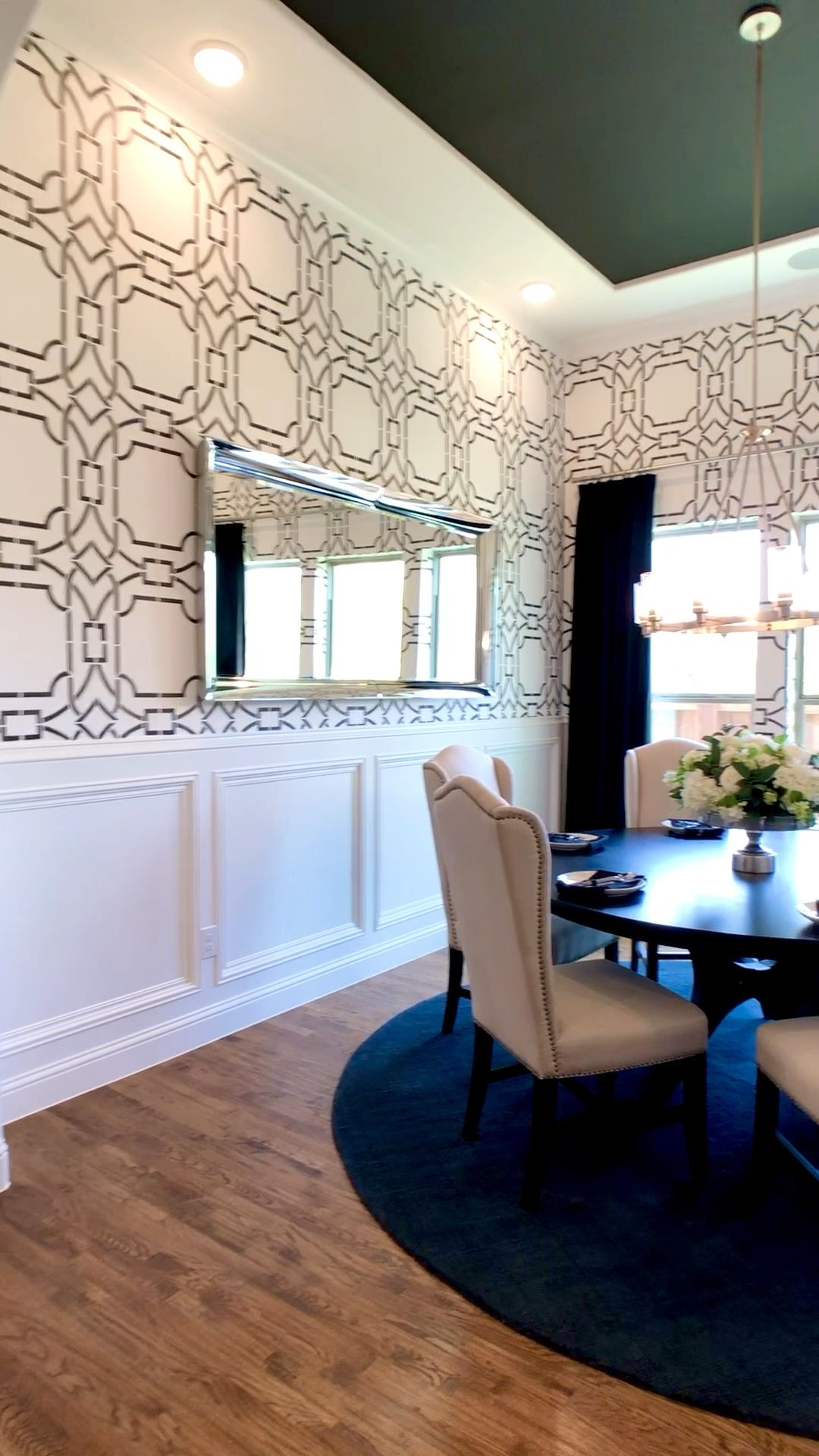 These black and white walls look like wallpaper, but the design was stenciled!  Beautiful wall molding, wood floors & dark ceiling complete this dining room decor.  Click to see more model home photos & get design inspiration...THE DECORATING COACH #decoratingideas #decoratingtips #diningroomideas #diningroomdecor