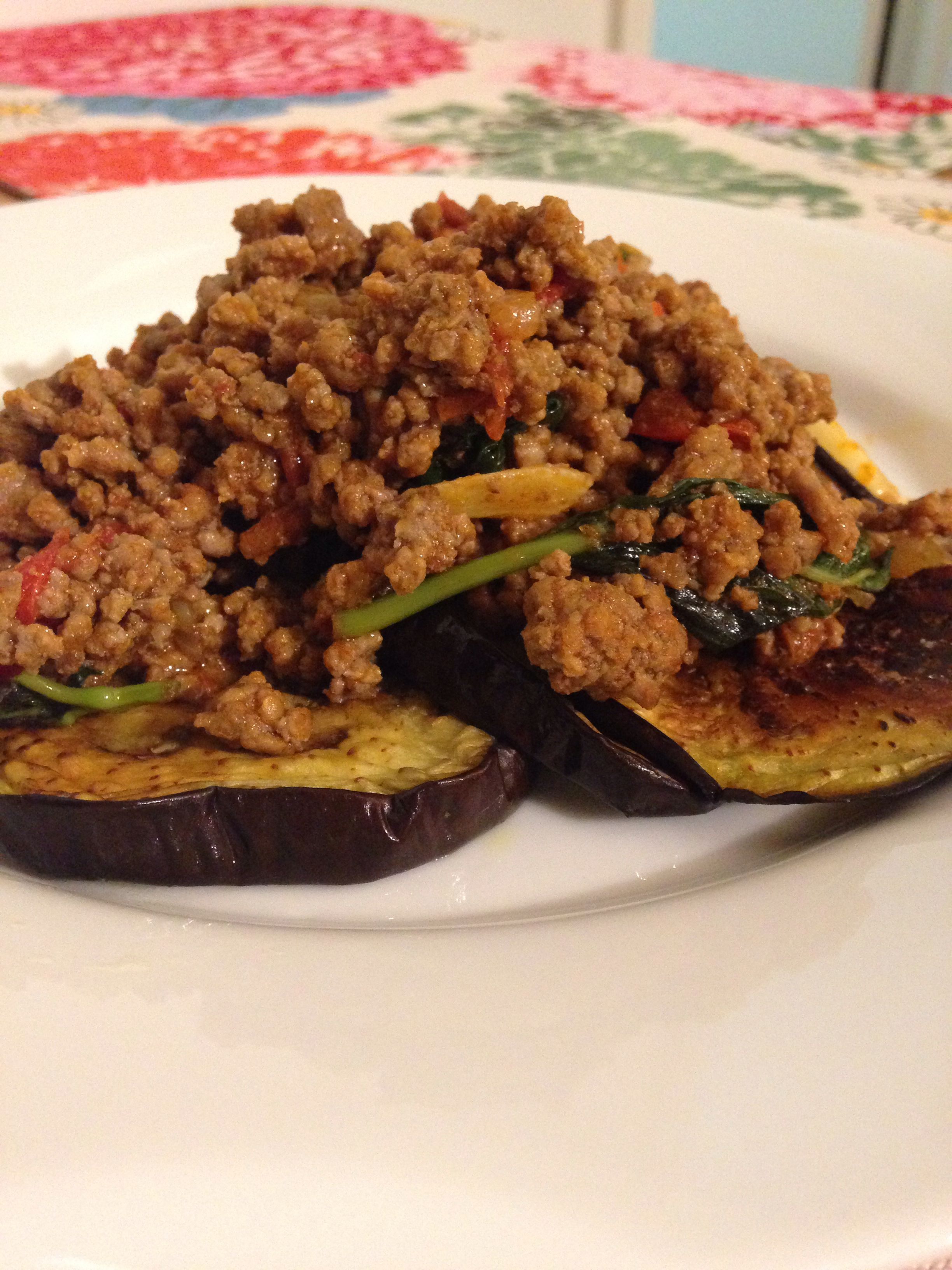 Baked eggplant topped with cumin ground beef mixed with tomatoes, garlic,onions, red peppers and basil. Yummy...
