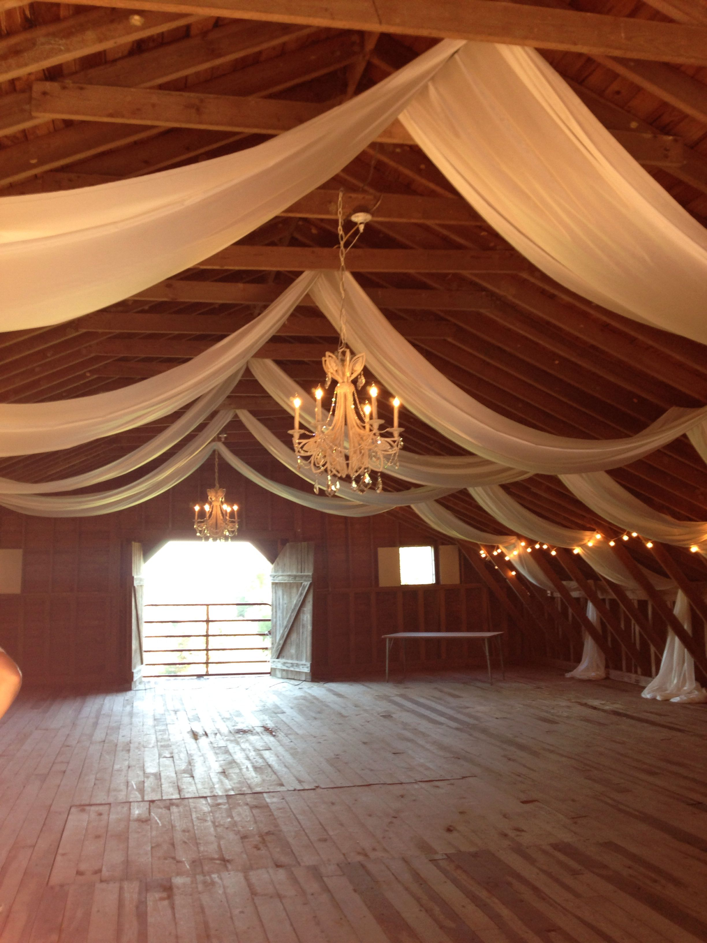 Wedding decorations tulle and lights  Fabric draped barn loft with chandeliers used for dance floor with