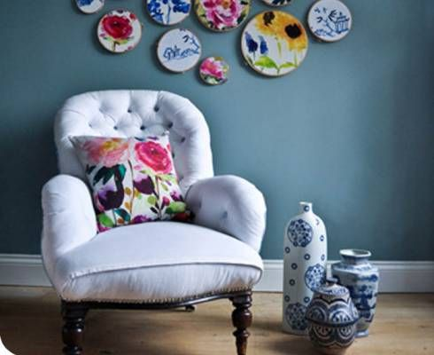 (Red Rose Square Linen Pillow - Gretel) Dusty blue wall, vignette collage of fabric around embroidery rings, white, comfy chair.