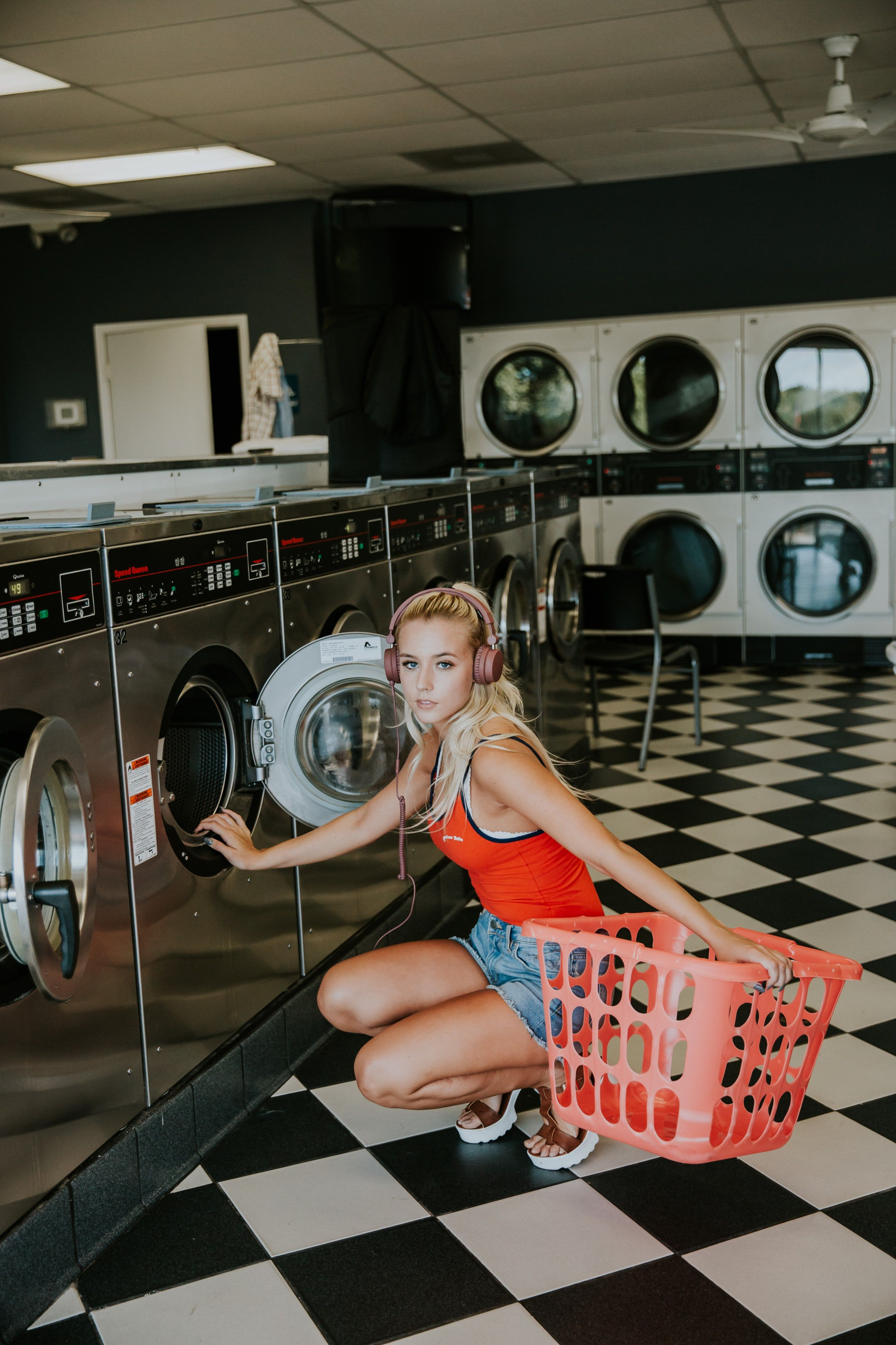 A Blonde Woman In Headphones Crouching Next To A Laundromat With A Laundry Basket Washing Clothes Laundry Shop Clean Washing Machine