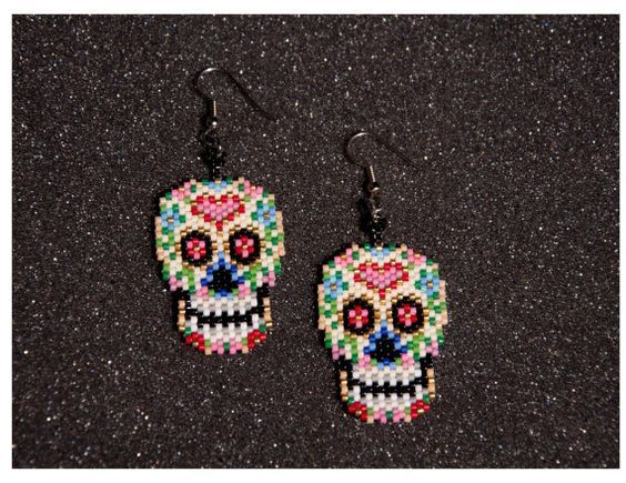 Skull measures approximately 1 wide and 1.5 long. Total length including ear hook is 2.5 long. Made by hand using nimo thread and delica
