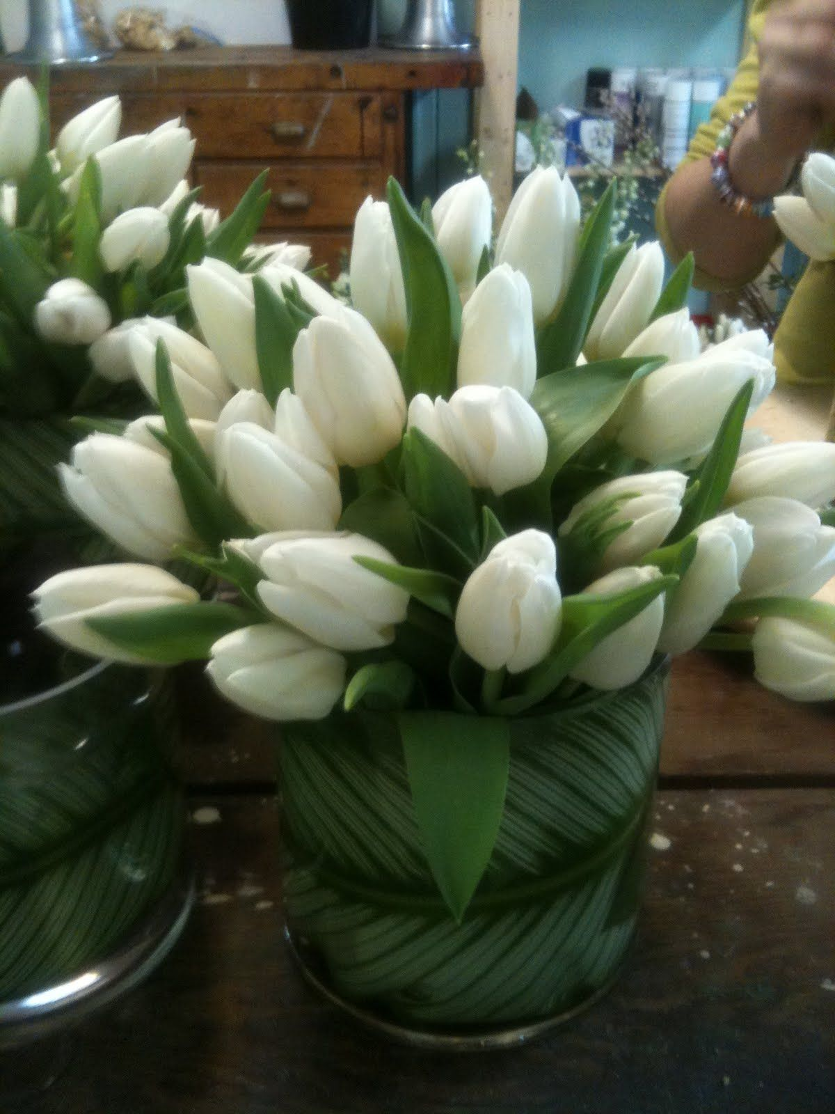 Minimal flower arrangement of white tulips with a patterned leaf wrap.