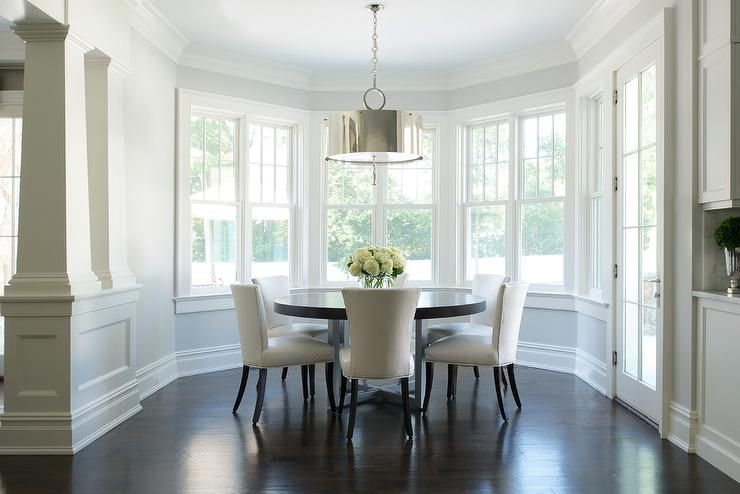 Curved Dining Room Features A Dark Stained Round Dining Table