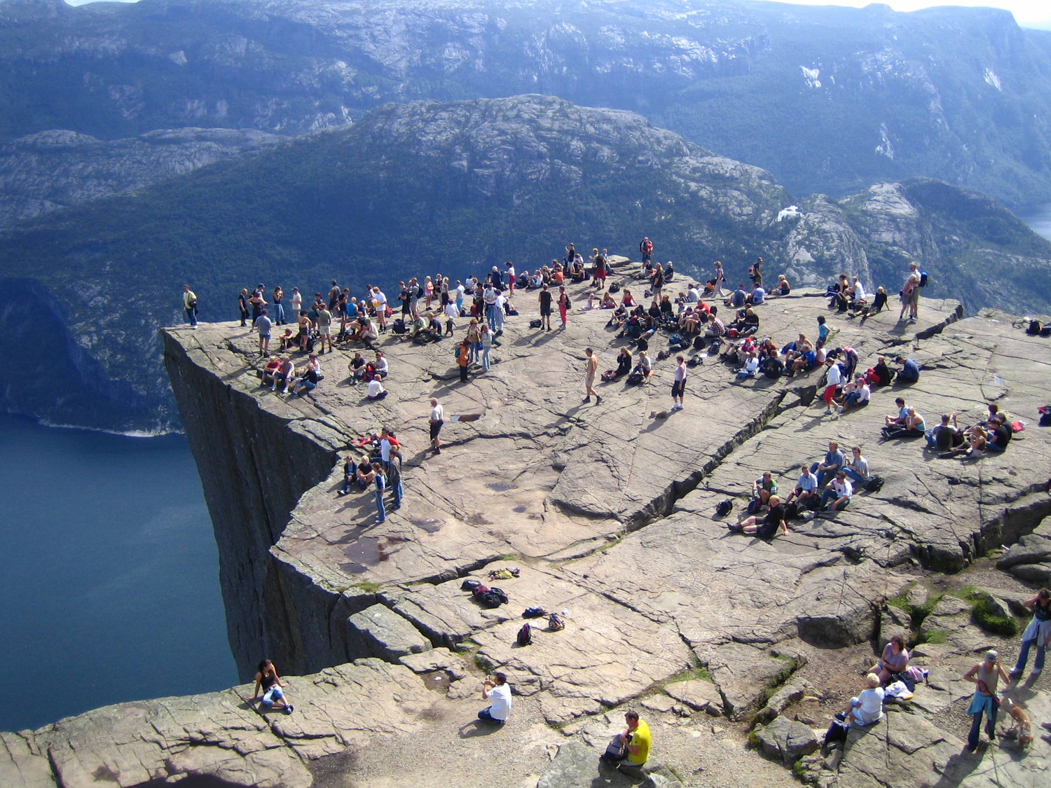 """Preikestolen or Prekestolen, also known by the English translations of Preacher's Pulpit or Pulpit Rock, and by the old local name Hyvlatonnå (""""the carpenter-plane's blade""""), is a massive cliff 604 metres (1982 feet) above Lysefjorden, opposite the Kjerag plateau, in Forsand, Ryfylke, Norway. The top of the cliff is approximately 25 by 25 metres (82 by 82 feet), almost flat, and is a famous tourist attraction in Norway."""