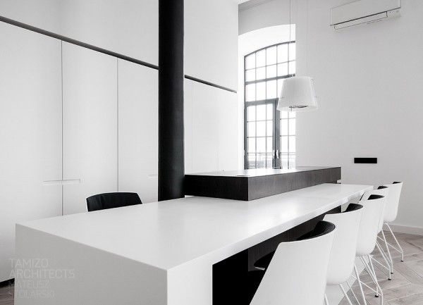 #reforma #cocina (presupuestON.com) en apartamento clásico rehabilitado de estilo minimalista en blanco y negro, isla y mesa de comedor integrada, módulos con paneles móviles para ocultar armarios y electrodomésticos.