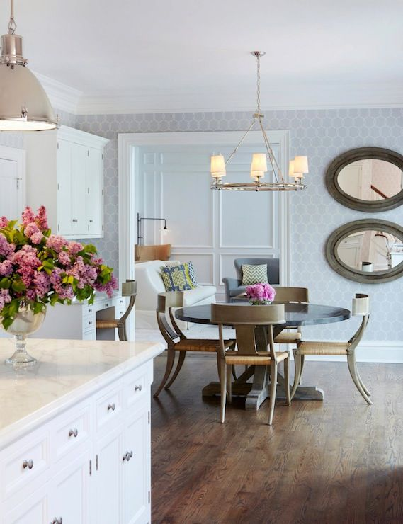 Chic Dining Room With Polished Nickel Ring Chandelier Over Salvaged Wood Cross Leg Table Surrounded