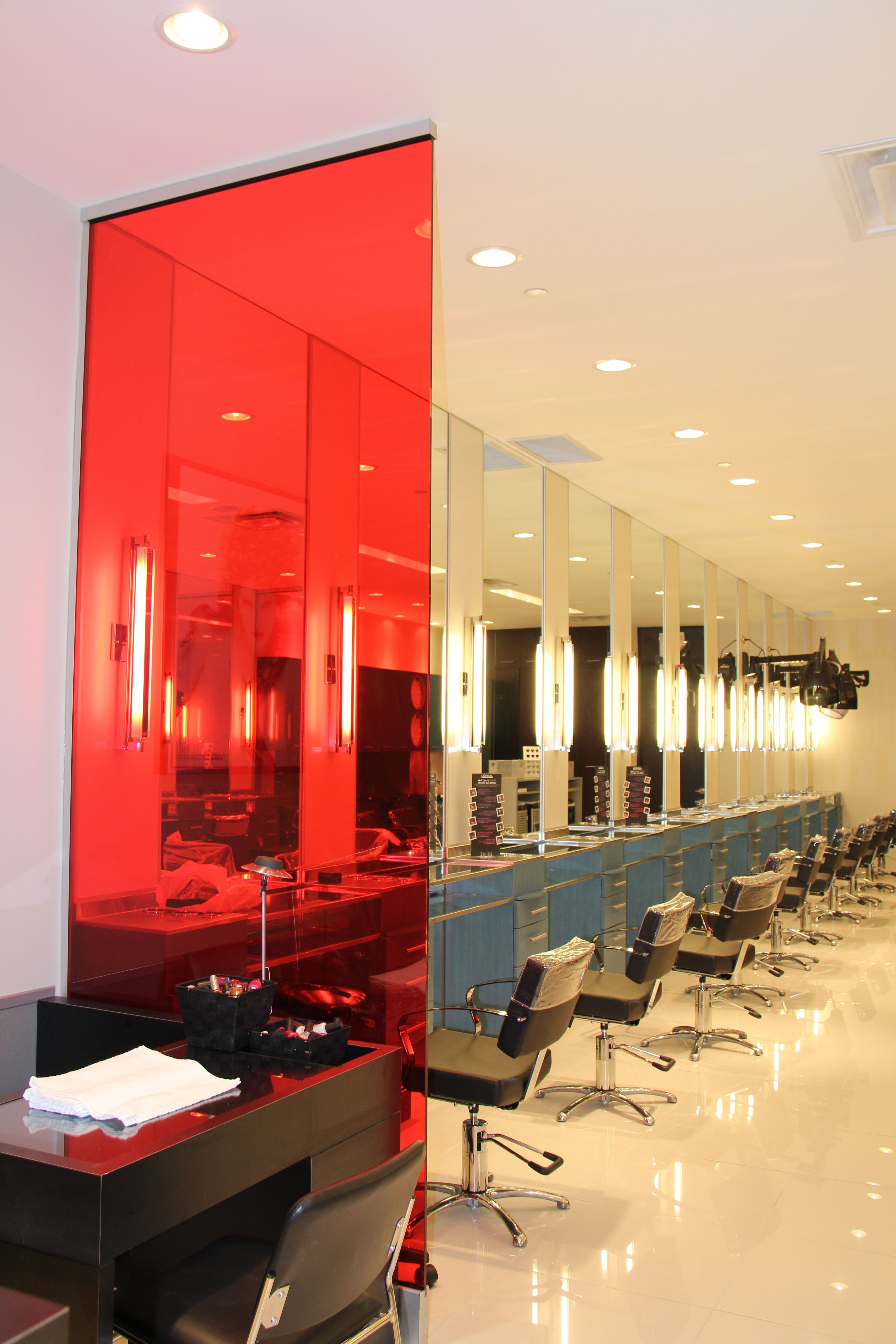 Rows of blue stylist stations with a prominent Red glass wall accent